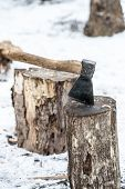 stock photo of ax  - Ax stuck in log of wood on the background of the winter forest and huts - JPG