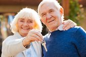 stock photo of bonding  - Happy senior couple bonding to each other and smiling while woman holding keys in her hand - JPG