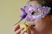 pic of purim  - Young Woman eat Hamantaschen cookie and wearing Purim jewish holiday carnival mask - JPG