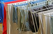 stock photo of wet pants  - Tight shot of an assortment of wet laundry on an indoor drying rack - JPG