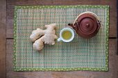 image of qi  - Pot of ginger tea, cup of tea with a piece of ginger in it and ginger root.