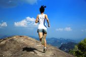image of cliffs  - young asian woman running on mountain peak cliff - JPG