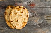 image of whole-grain  - Simply delicious baked crusty whole grain naan flatbreads a leavened bread cooked in a tandoor clay oven served on authentic old wooden Picnic Table shot from above with copyspace on the right - JPG