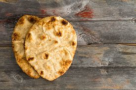 stock photo of whole-grain  - Simply delicious baked crusty whole grain naan flatbreads a leavened bread cooked in a tandoor clay oven served on authentic old wooden Picnic Table shot from above with copyspace on the right - JPG