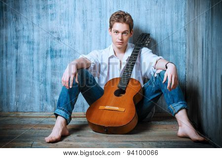 Romantic young man playing an acoustic guitar, sitting on the wooden floor