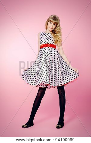 Full length portrait of a pretty teenager girl posing in pin-up dress over pink background.