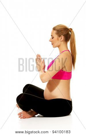 Pregnant woman in lotus position exercising yoga
