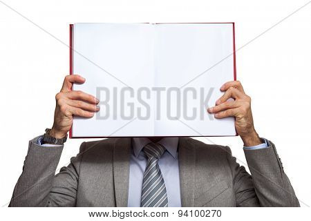 Portrait of a businessman holding a book in front of his face