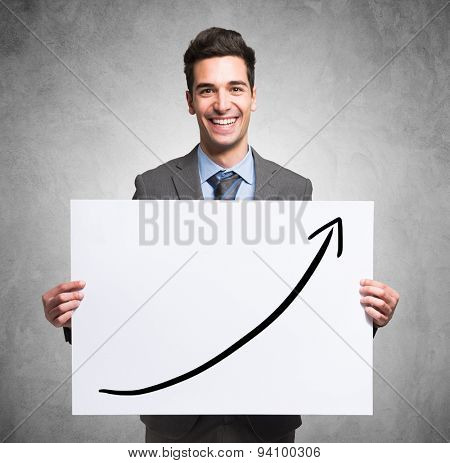 Portrait of a smiling young businessman holding a panel with a rising arrow on it