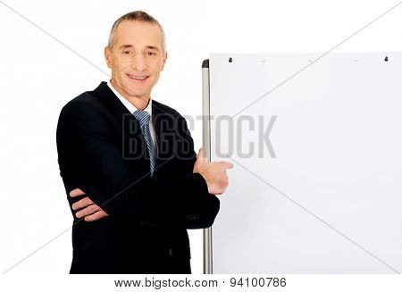 Mature businessman with marker pointing on flip chart.