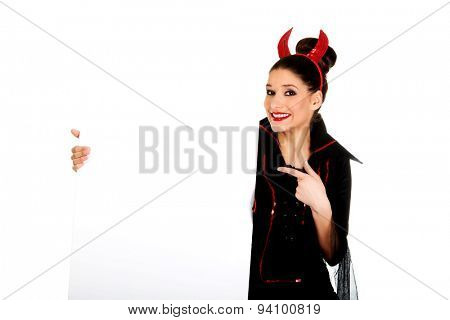 Woman in devil carnival costume with empty banner.