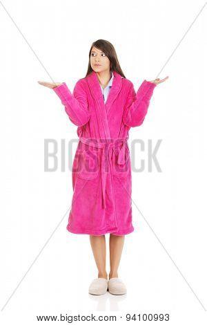 Beautiful woman in pink bathrobe showing empty palms.