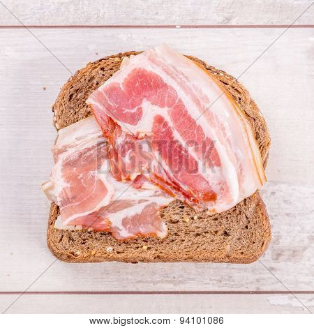 Sandwich with bacon on wood background.