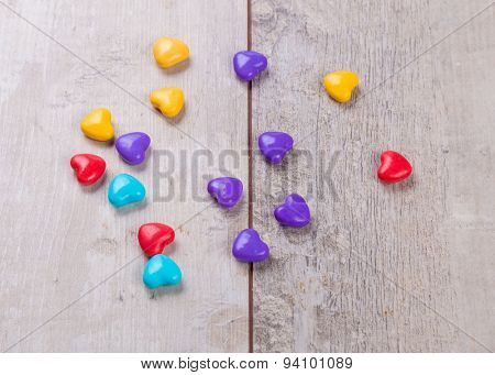 Heart shaped valentine candy on wooden background
