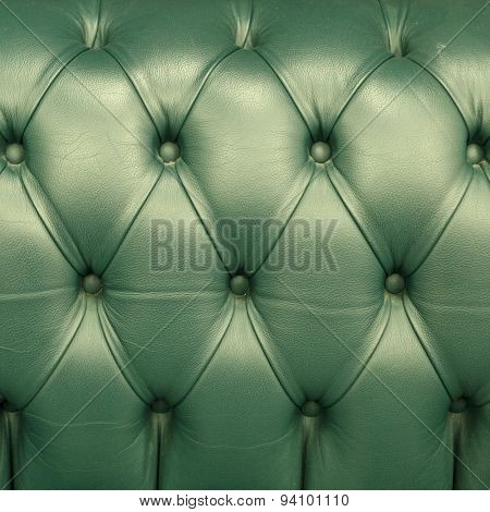 horizontal background with olive chesterfield leather close-up