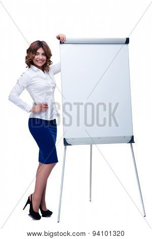 Full length portrait of a happy beautiful businesswoman standing with blank flipchart isolated on a white background. Looking at camera