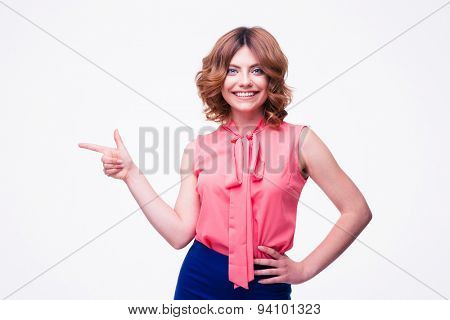 Happy woman pointing finger away isolated on a white background. Looking at camera