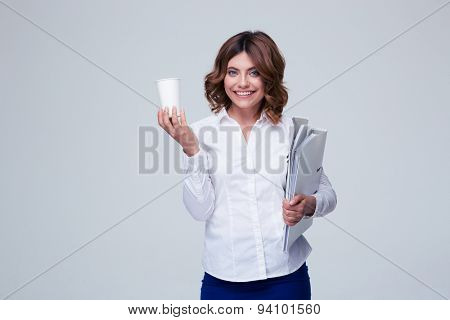 Smiling businesswoman holding folders and cup with coffee over gray background. Looking at camera