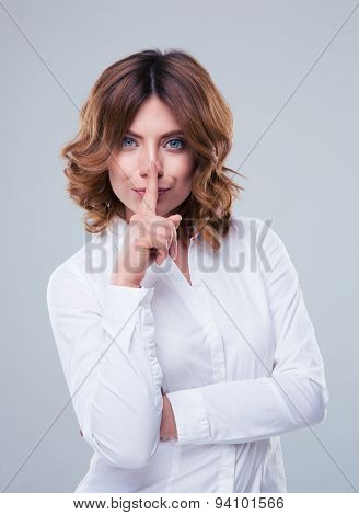 Cute businesswoman showing finger over lips over gray background. Be quiet! Looking at camera