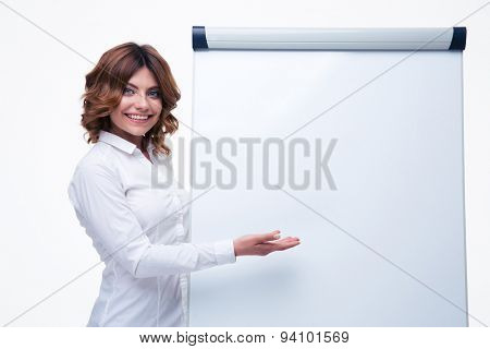 Smiling businesswoman presenting strategy on blank flipchart isolated on a white background. Looking at camera