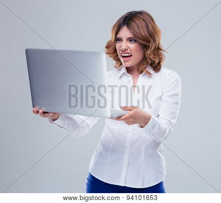 Businesswoman with disgusted emotion holding laptop over gray background
