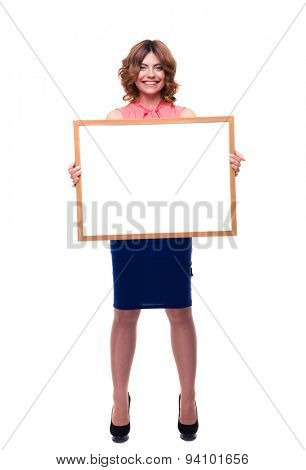 Full length portrait of a happy casual woman holding whiteboard isolated on a white background. Looking at camera