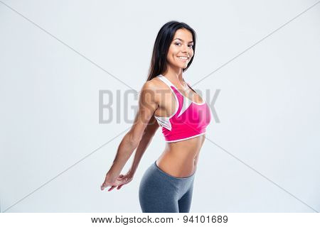 Happy fitness woman stretching hands over gray background. Looking at camera