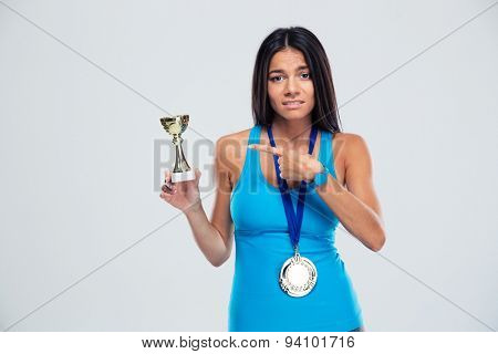 Sports woman pointing finger on the winners cup over gray background and looking at camera