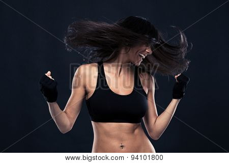 Portrait of a woman dancing with hair in motion over black background