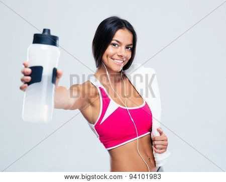 Happy fitness woman holding bottle with water over gray background. Looking at camera