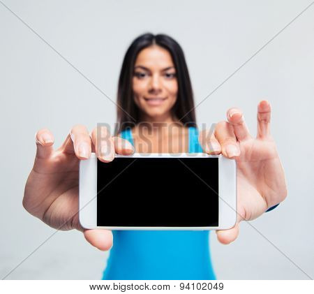 Smiling woman showing blank smartphone screen over gray background. Looking at camera. Focus on smartphone