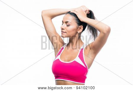 Fitness woman making ponytail isolated on a white background
