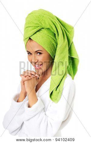 Spa woman in bathrobe clenching hands.