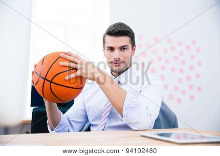 Handsome businessman sitting at the table and holding ball in office