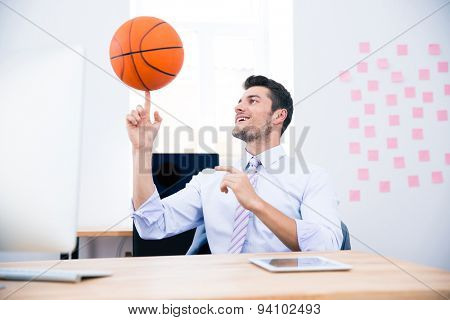 Smiling businessman sitting at the table and spining ball in office