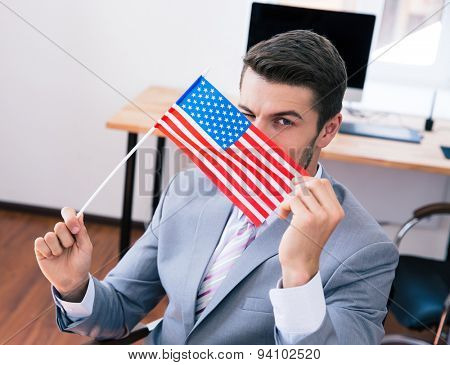 Businessman in suit holding USA flag in office