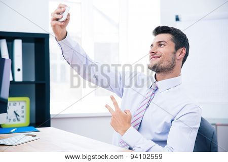 Smiling businessman sitting at the table and making selfie photo on smartphone in office