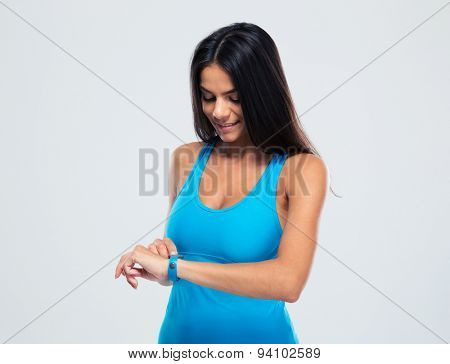 Happy sporty woman using fitness tracker over gray background