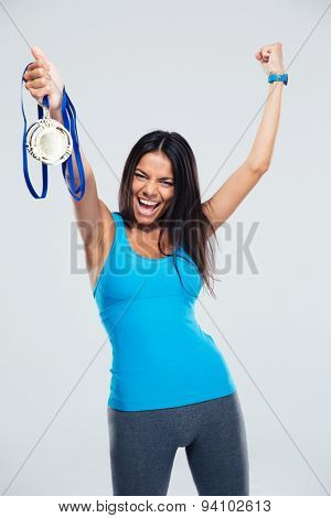 Sports woman celebrating his success with medal ocer gray background