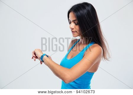 Fitness woman using fitness tracker on wrist over gray background