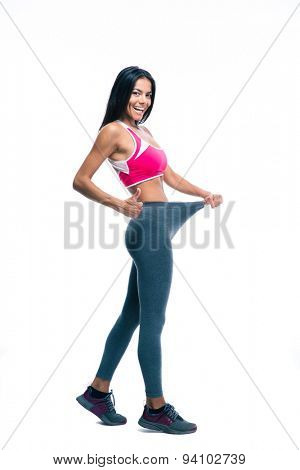 Cheerful sporty woman showing big pants and showing thumb up isolated on a white background