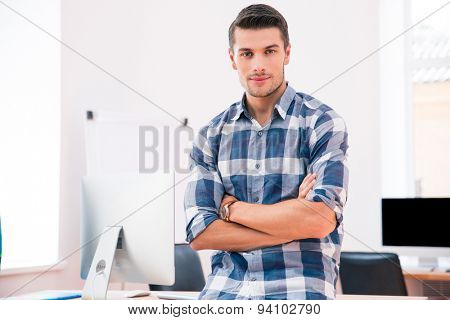 Portrait of a handsome businessman in casual cloth with arms folded in office. Looking at camera