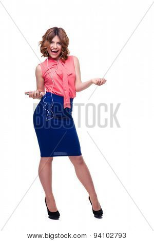 Full length portrait of a cheerful young woman listening music in headphones isolated on a white background