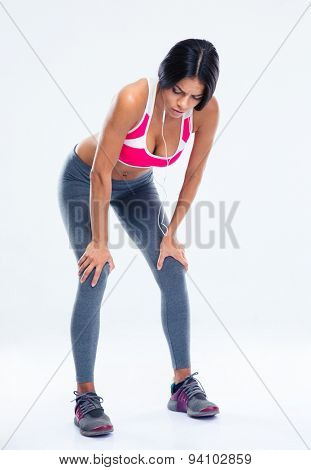 Full length portrait of a tired fitness woman resting over gray background