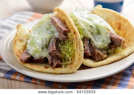 Two Gyros with meat and tzatziki sauce on a plate