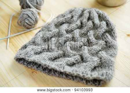Knitted hat and knitting needles on a table