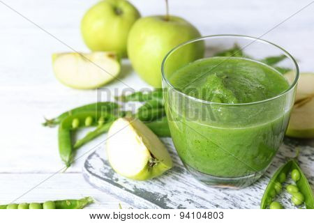 Healthy green smoothie with peas and apples on wooden table, closeup