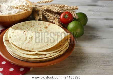Stack of homemade whole wheat flour tortilla and vegetables on plate, on wooden table background