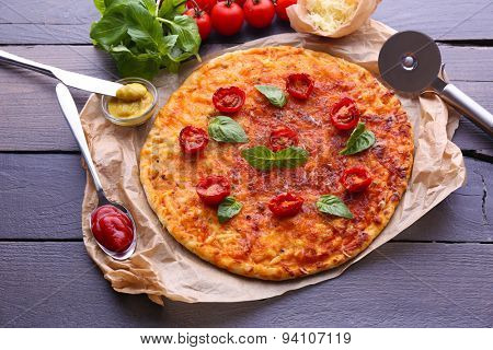 Pizza with basil and cherry tomatoes on parchment on wooden table background