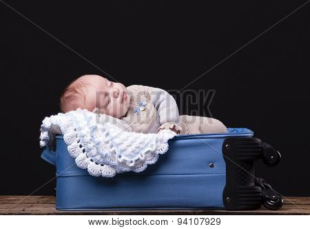 Newborn baby sleeping inside trolley bag